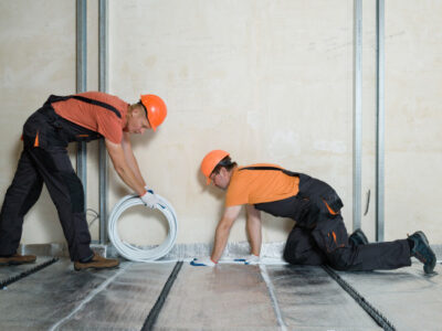 workers-are-installing-pipe-warm-floor-apartment_191163-1041